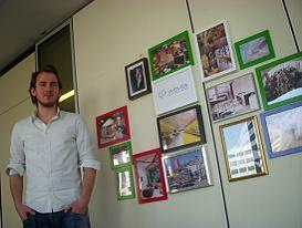 Floris posing in front of our Wall of Workplaces we like
